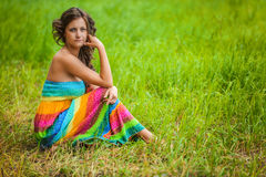 Woman in colorful dress sitting on grass Stock Photography