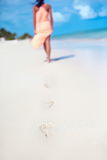 Woman in colorful dress walking on beach ocean leaving footprints Stock Photos