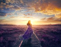 Woman in colorful dress walking. A woman in a colorful purple dress walks to a beautiful sunset royalty free stock images