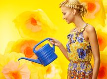 Woman in colorful dress among yellow flowers Stock Images