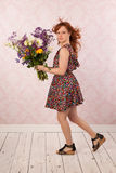 Woman with colorful flowers. Woman in interior with colorful bouquet flowers Stock Image