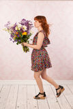 Woman with colorful flowers. Woman in interior with colorful bouquet flowers Stock Photos