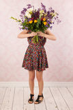 Woman with colorful flowers. Woman in interior with colorful bouquet flowers Stock Photography