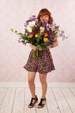 Woman with colorful flowers. Woman in interior with colorful bouquet flowers Royalty Free Stock Photography