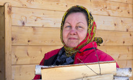 A woman in a colorful handkerchief bears birch firewood Royalty Free Stock Photo