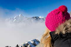 Woman with colorful hat overlooking winter mountains Royalty Free Stock Photo
