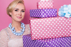 Woman with colorful jewelry holding big and small present boxes. Soft colors. Christmas, birthday, Valentine day. Studio portrait over pink background royalty free stock photos