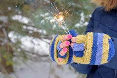 Woman in knit gloves holding sparklers in the snow. Woman in colorful knit fingerless gloves celebrating with sparklers in the snow Stock Photo