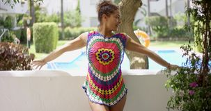 Woman in colorful knit top stretching on balcony stock video footage