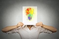 Woman with colorful lightbulb covering face. Woman having brilliant idea colorful lightbulb covering face isolated grey wall background. Free thinking, new Stock Photography