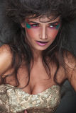 Woman with colorful make up looking away from the camera. Close up picture of a beauty woman with colorful make up and cool hairstyle looking away from the Stock Image