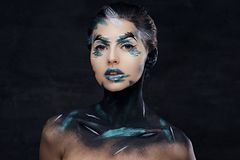 A woman with colorful make up and painted art on a neck. Studio portrait of young female with colorful make up and painted art on a neck Stock Photography