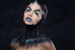 A woman with colorful make up and painted art on a neck. Studio portrait of young female with colorful make up and painted art on a neck Stock Photo