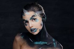 A woman with colorful make up and painted art on a neck. Studio portrait of young female with colorful make up and painted art on a neck Royalty Free Stock Images