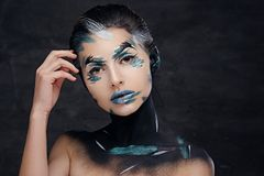 A woman with colorful make up and painted art on a neck. Studio portrait of young female with colorful make up and painted art on a neck Royalty Free Stock Image