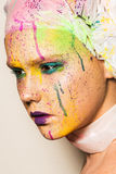 Woman with colorful makeup. Close-up portrait of young woman with unusual makeup. Model posing with paint drops over her face. Creative makeup Stock Photography