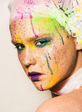Woman with colorful makeup. Close-up portrait of young woman with unusual makeup. Model posing with paint drops over her face. Creative makeup Royalty Free Stock Photo