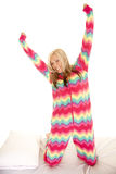 Woman in colorful pajamas kneel on bed stretch Royalty Free Stock Image