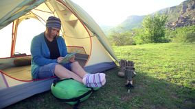 Woman in colorful socks and kerchief sits in a tent and looks on map in her hands under sunlight. stock video footage