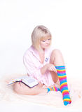 Woman in colorful strip socks reading a book Stock Photos