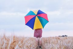 Woman with colorful umbrella in the field, optimistic positive concept. Woman with colorful umbrella in the field, optimistic positive multicolored background Stock Photos