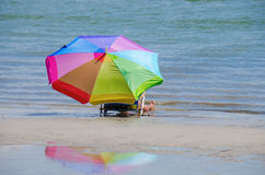 Woman and colorful umbrella by the shoreline Stock Photo