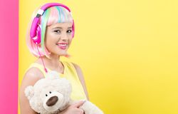 Woman in a colorful wig holding a teddybear stock photo