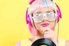 Woman in a wig holding a vinyl record. Woman in a colorful wig holding a vinyl record on a purple background royalty free stock images