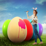 Woman coloring Easter eggs Stock Photo
