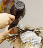 Woman with coloring foil. On her hair in salon Royalty Free Stock Image