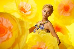 Woman in colourful dress among yellow flowers Stock Image