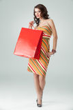 Woman colourful outfit holding red shopping bag. Portrait of a young woman holding in one hand a red shopping bag and the other one on her hip. she is laughing Stock Image