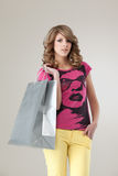 Woman in colourful outfit holding shopping bag Stock Photos