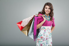 Woman in colourful outfit holding shopping bags. Studio portrait of a young woman in a colourful outfit, holding in one hand three shopping bags. she is laughing Stock Images
