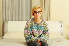 Woman in colourful sweater sitting on the bed Royalty Free Stock Photography