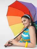 Woman with a colourful umbrella Stock Images