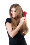 Woman with comb. Young woman combing her long hair royalty free stock image