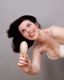 Woman with comb. Smiling hapy woman with comb Royalty Free Stock Image