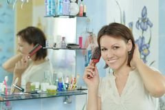 Woman comb her hair in a bathroom Royalty Free Stock Photo