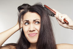 Woman with comb in her hands Royalty Free Stock Images