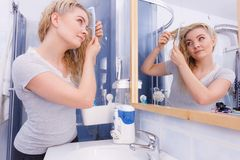 Woman combing her long hair in bathroom royalty free stock photos