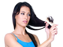Woman combing ends of her hair Royalty Free Stock Image
