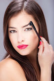 Woman combing eyebrow. Pretty woman combing her eyebrow Royalty Free Stock Images