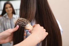 Woman combing friend`s hair with cushion brush indoors. Closeup royalty free stock images
