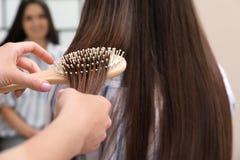 Woman combing friend`s hair with cushion brush indoors. Closeup stock photos