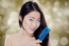 Woman combing her black hair Stock Photography