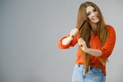 Woman combing her brown hair Royalty Free Stock Photography