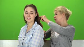 Woman is combing her daughter. Green screen. Woman is combing her daughter, they are talking to each other sitting on a white wooden bench. Green screen stock footage