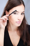 Woman combing her eyebrow. Pretty woman combing her eyebrow Stock Photo