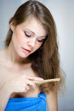 Woman combing her hair. Attractive woman combing her hair by wooden hairbrush Royalty Free Stock Photos